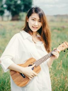 草地上的尤克里里白衬衫美女纯真图片