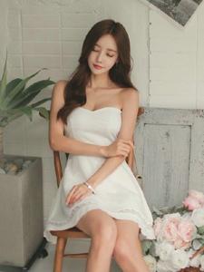 抹胸白色连衣裙模特安详的坐在椅子上