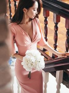 楼梯上的捧花露背裙美模勾勒出背部完美的曲线