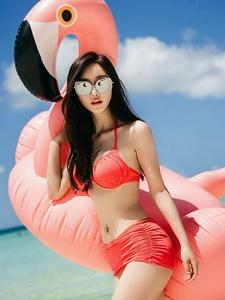 沙滩比基尼墨镜美模躺在游泳圈上晒阳光