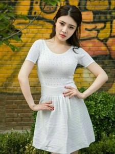 戶外涂鴉墻前清純白裙嫩模雙手叉腰顯纖細美腰