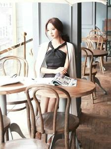 餐厅内坐在凳子上的墨镜模特倚靠在墙上休闲自然