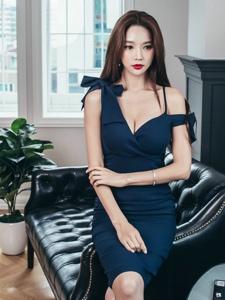 端坐在沙发上的深蓝裙美模乳沟若隐若现