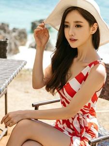 烈日下海边的遮阳帽美模坐在椅子上悠闲自在
