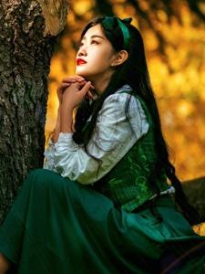 秋天落叶丛中的童话般红唇少女