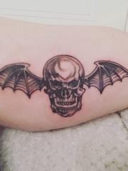 男性大腿上黑色的骷髅头纹身恶魔翅膀纹身图片