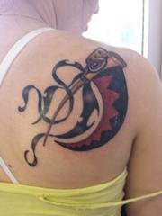 女性右后肩背上彩色的噬魂者的刀纹身图片