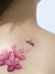 女生背部一只蜜蜂和花卉纹身图案