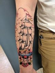男性手臂上帅气的彩色纹身小帆船图片