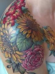 女性右肩臂上漂亮的彩绘纹身小花朵图片