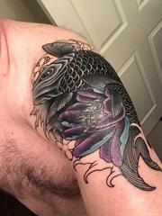 男子肩膀上的大黑色鲤鱼和蓝紫色莲花纹身