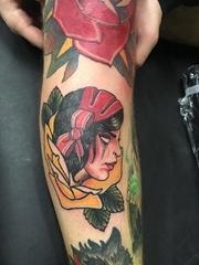 花臂膀上的红色和黄色玫瑰花里的女子肖像纹身