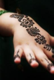 女生手背上黑色抽象线条精致花朵纹身图片