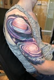 男生手臂上彩绘渐变抽象线条宇宙和星球纹身图片