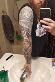 文艺花臂纹身男生手臂上黑色的骷髅花臂纹身图片