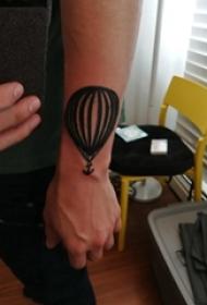 男生手臂上黑色简单线条船锚和热气球纹身图片