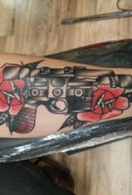 手臂纹身图片 男生手臂上花朵和手枪纹身图片