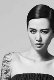 中國紋身明星 譚維維手臂上黑灰色的浪花紋身圖片