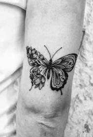 大臂后侧部的手肘拐处的一组小黑图纹身图案