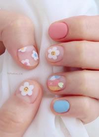 小花朵搭配笑脸元素的可爱美甲