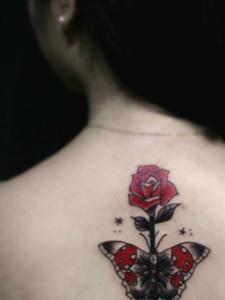 红玫瑰和蝴蝶结合的背部纹身