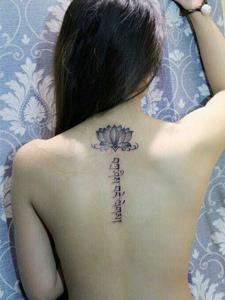 女生脊椎部荷花和梵文結合的紋身