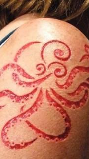 大臂上个性另类的章鱼图腾割肉纹身
