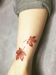 落在腿部的两片树叶纹身图片