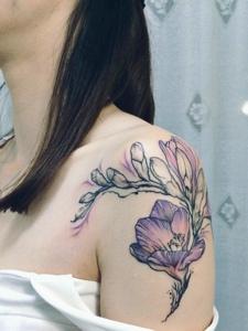 女生香肩下的美麗蘭花紋身圖案