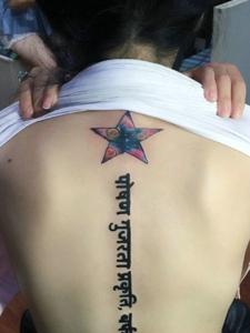 脊椎部彩色五角星與梵文的紋身圖案