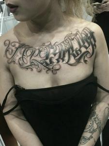 个性女孩胸前带点弧度的花体英文纹身