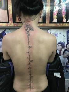盘发女子脊椎部英文纹身图案